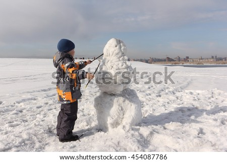The little boy in a color jacket building a snowman on the river bank in the winter - stock photo