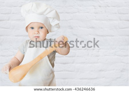 The little boy in a suit of the cook sculpts dough. Baby make dinner in chef suit. Cooking concept with free text space - copy space - stock photo