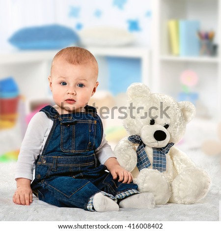 the little boy in blue overalls plays with a teddy bear. Kid having fun at home - stock photo