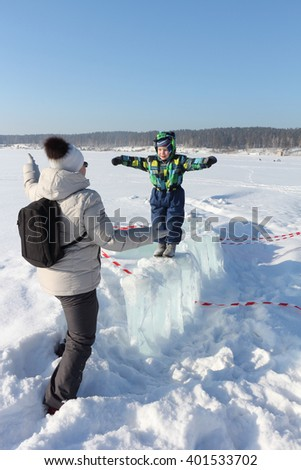 The little boy in color overalls going on an ice  towards to the woman with a backpack - stock photo