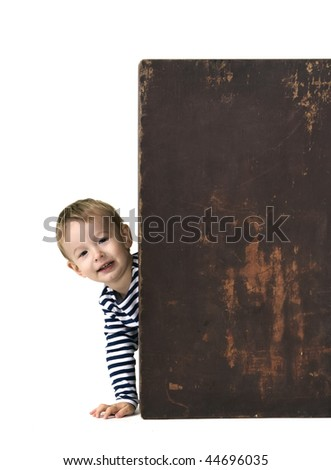 The little boy looks out of the big box - stock photo