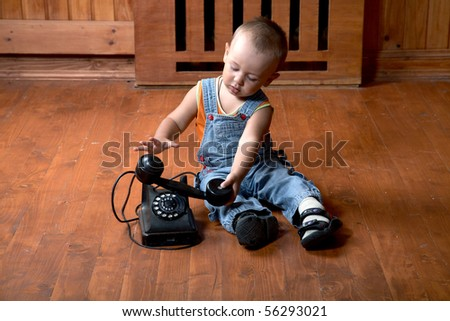 The little boy plays old phone sitting on a floor - stock photo