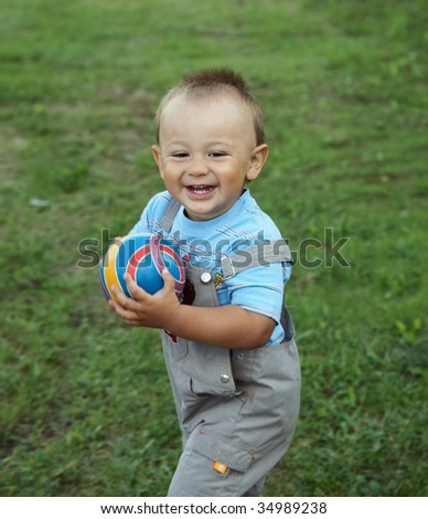 The little boy plays with  ball on green grass - stock photo