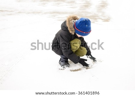 The little boy plays with snow in the backyard. Dressed in a black jacket and blue cap