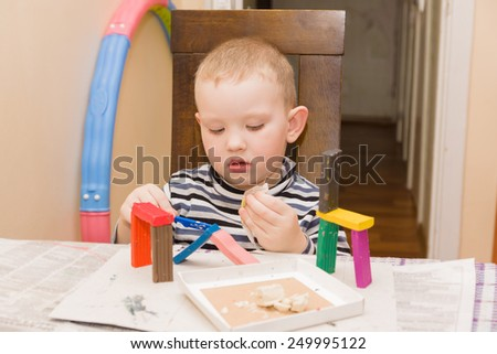 the little boy sits at a table and is engaged in a molding from plasticine - stock photo