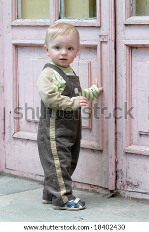 The little boy sits near a door - stock photo