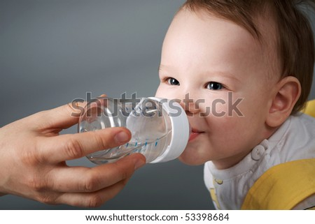 The little boy smiled and drank water from a bottle. Close-up. - stock photo
