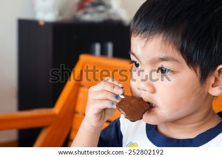 The little boy think and eating chocolate  - stock photo