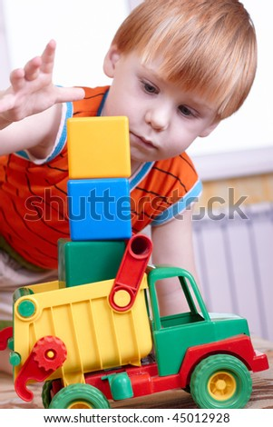 The little boy with a toy on a sofa - stock photo