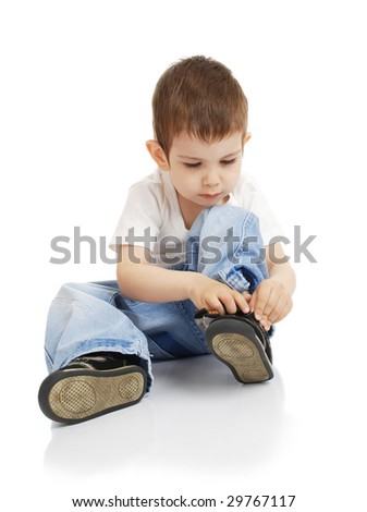 The little boy without assistance dresses shoes