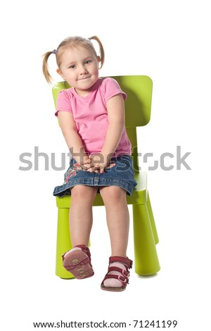 the little child sits on a chair - stock photo