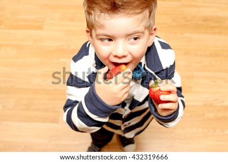 The little cute boy of four years old dressed in classic clothes, looks up and tries to eat the strawberries - stock photo