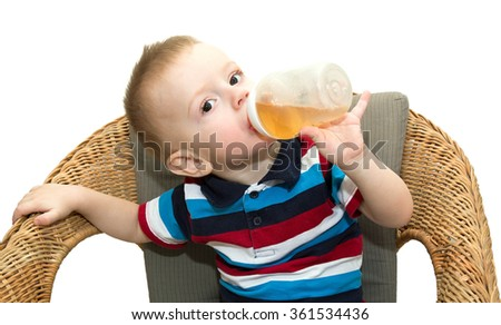 The little fair-haired boy sits in a wicker chair and drinks juice from a small bottle. It is isolated on a white background - stock photo