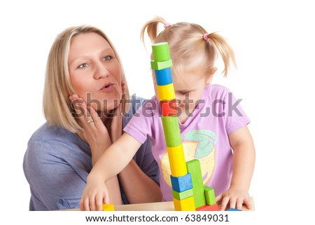 the little girl and her mother playing with toy blocks