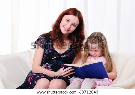 The little girl and her mother read a book together on the couch - stock photo