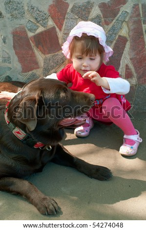 The little girl and the labrador against stone wall. Shallow DOF, focus on dog - stock photo