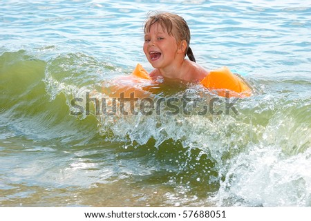The little girl bathes in waves - stock photo
