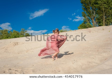 The little girl cheerfully runs on sand. Wind blows a bright scarf on the girl - stock photo