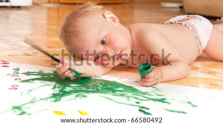 The little girl draws lying on a floor - stock photo