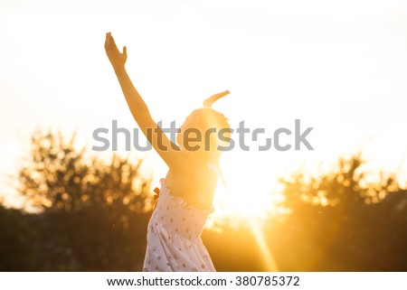 The little girl enjoys the sunset, she looks up and spreads his hands with pleasure - stock photo