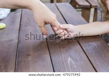 The little girl happy with curly golden hair holding the hand of his mother.