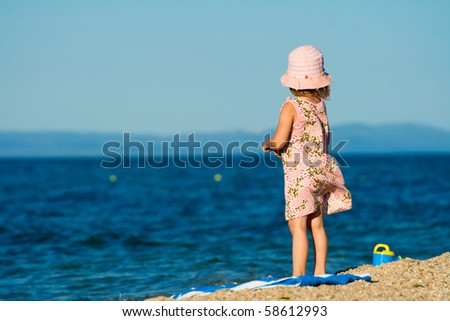 The little girl in a beautiful dress and hat standing on the beach and looks into the distance. - stock photo