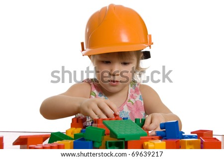 The little girl in a helmet plays - stock photo
