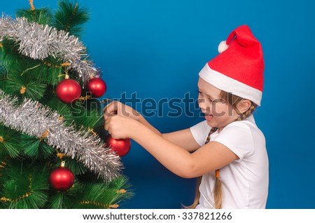 The little girl in a red cap hangs up on a fir-tree with tinsel a toy and smiles. Christmas. - stock photo