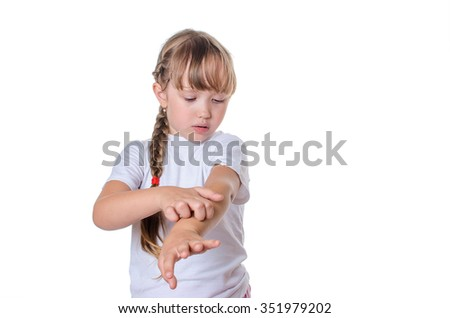 The little girl in a white undershirt scratches a hand