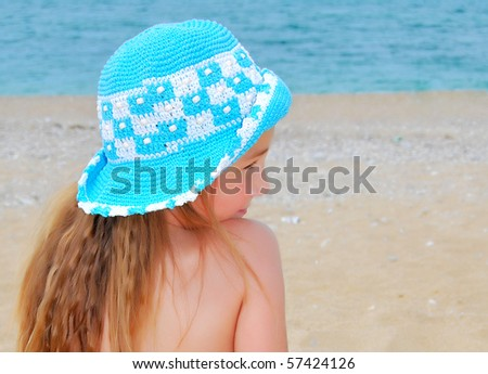 the little girl in hat on the beach