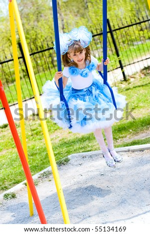 The little girl in holiday attire swing - stock photo