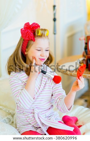 the little girl in pin up style in a striped terry dressing gown, in hair curlers and with a red bandage in peas looks in a small pocket mirror with a red brush for powder