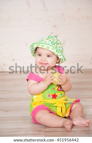 the little girl in the hat sitting on the floor