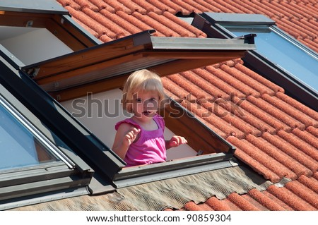 The little girl in the roof window .