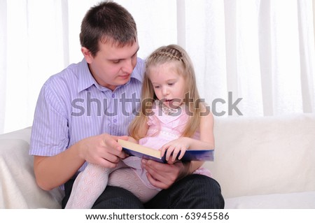 The little girl is sitting on the lap of his father, and reads with him a book. - stock photo
