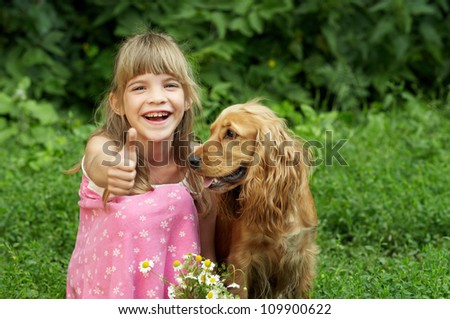 The little girl is smiling and sumbup in the garden with the dog - stock photo