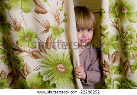 The little girl looks out because of curtains - stock photo