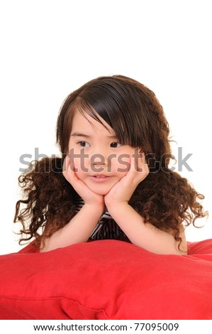 The little girl lying on red pillow - stock photo