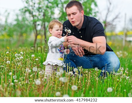 The little girl makes a wish. The father and the kid sit on a green grass. - stock photo