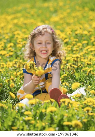 The little girl on a glade with dandelions - stock photo