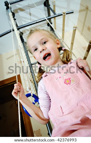 The little girl on a sports swing