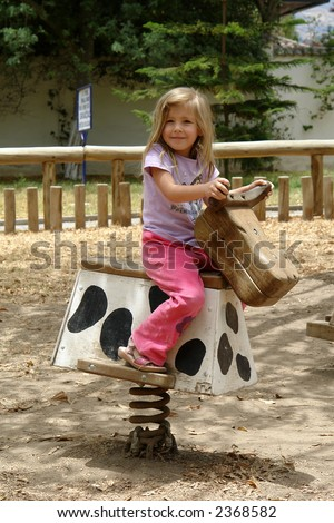 the little girl on the horse - stock photo