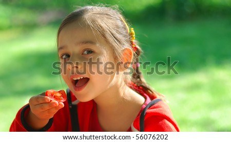 The little girl sits at table in garden and eats tomato. - stock photo