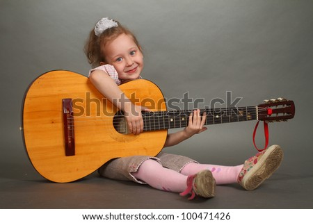 the little girl sits on a floor with a big guitar, a look in a lens