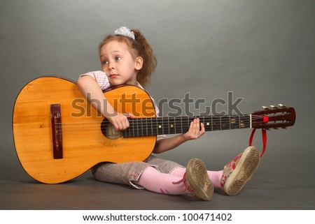 the little girl sits on a floor with a big guitar, a look not in a lens, a double 2