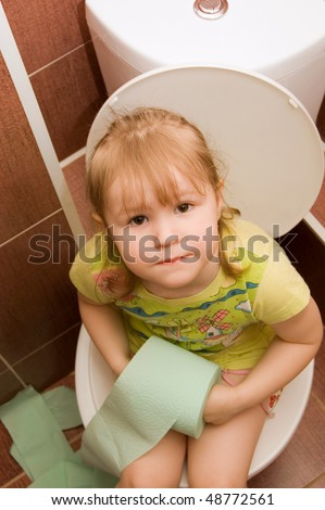 The little girl sits on a toilet bowl