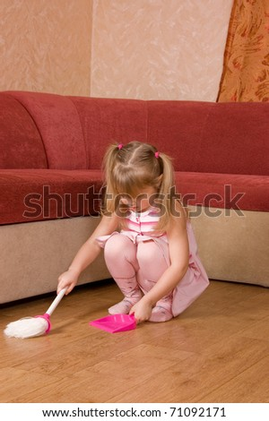 The little girl sweeps a floor - stock photo