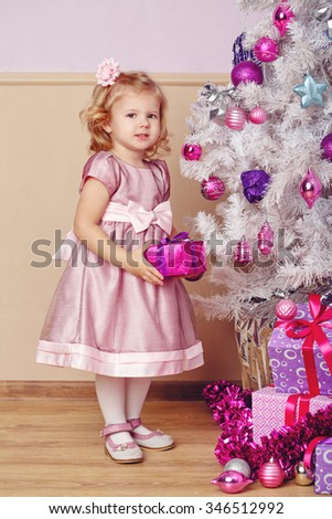 The little girl took the gift from under the Christmas tree. New Year. Holiday and fun. Merry Christmas. 2017 - stock photo