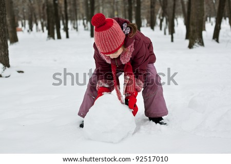 The little girl was lying a snowman in winter - stock photo