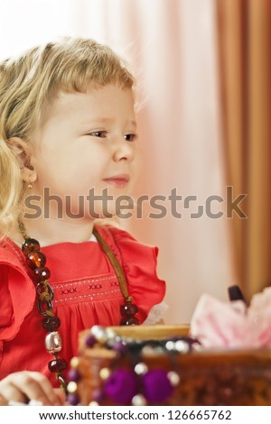 The little girl with a beads looking at herself in a mirror - stock photo